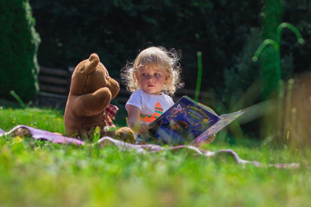 Une petite fille qui lit un livre avec son doudou pendant un pique-nique